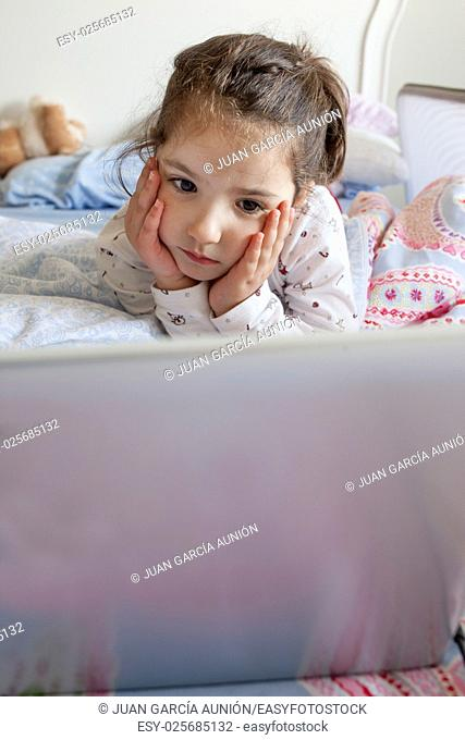 Little girl lying in bed and playing with a laptop in his bedroom. She looks attentive