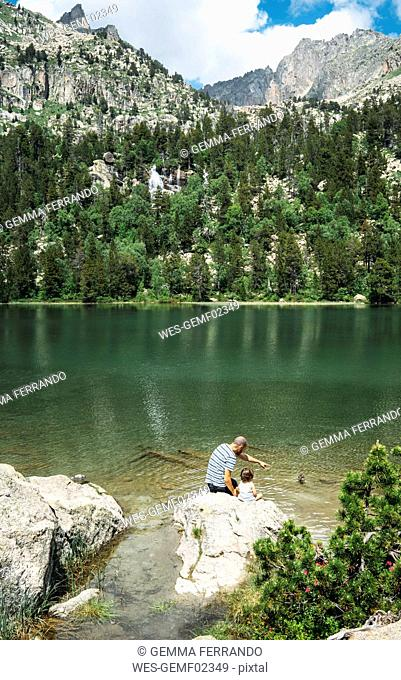 Spain, Father and daughter sitting on a rock at a mountain lake, feeding ducks