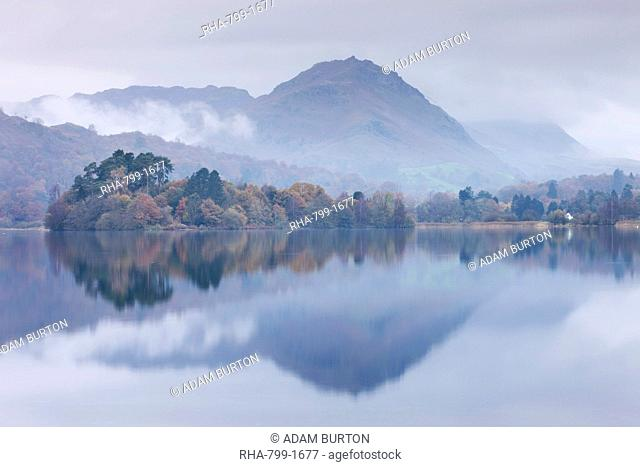 Mist hangs over the lake and island at Grasmere with Helm Crag beyond, Lake District, Cumbria, England, United Kingdom, Europe