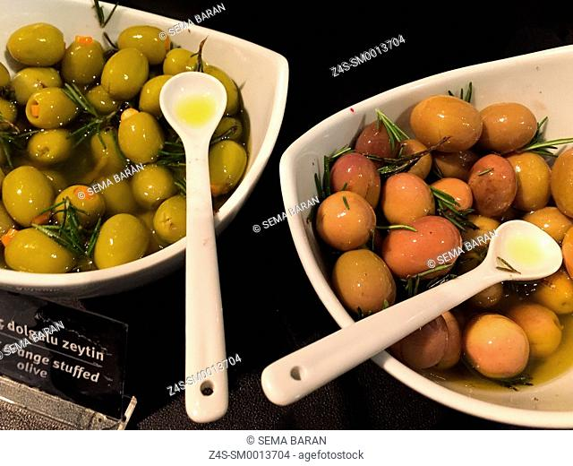 Stuffed olives with olive oil and rosemary in white ceramic bowls