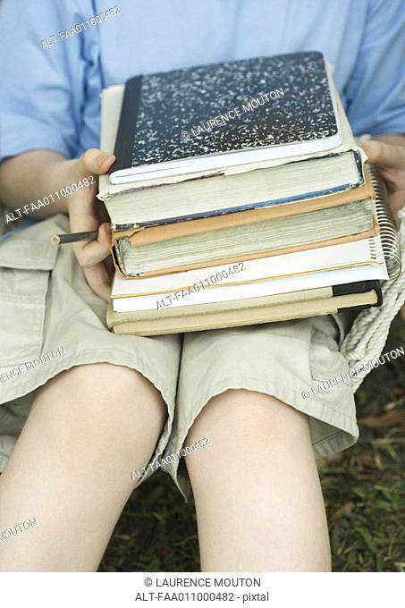 Child holding stack of books and notebooks on lap