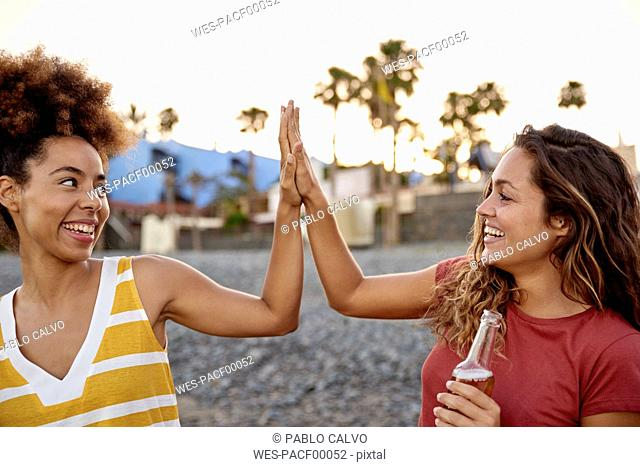 Two best friends high fiving on the beach