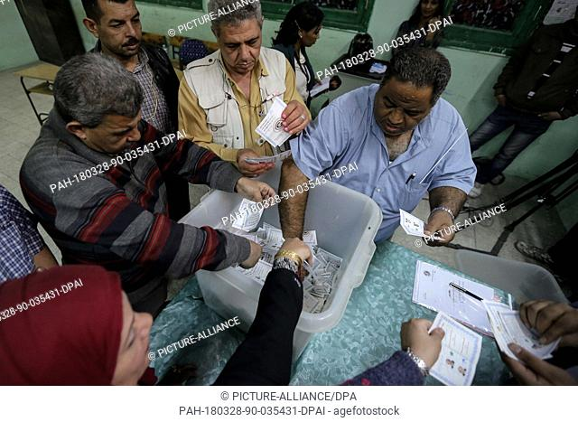 Election officials empty a ballot box before starting to count votes at the end of the third and final day of Egypt's presidential elections