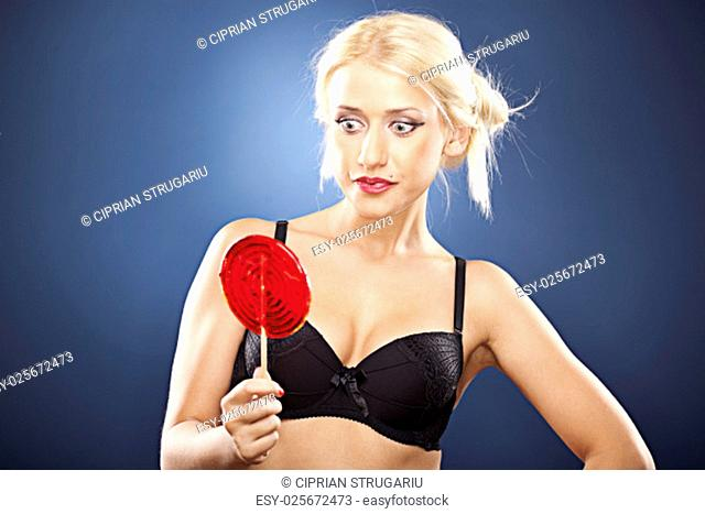 Beautiful blonde model, in back bra, looks at a red lollipop