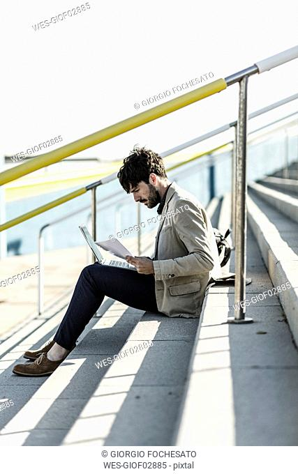 Pensive man sitting on steps outdoors checking documents