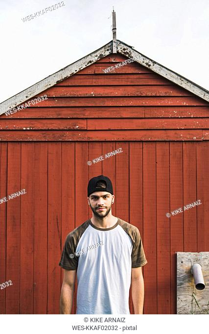 Young man standing in front of red barn, portrait