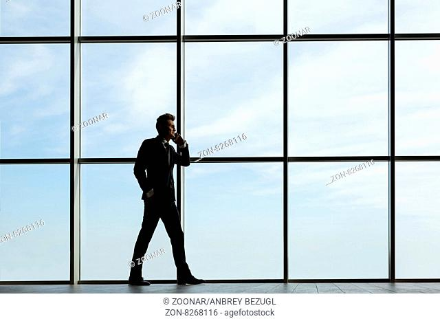 Silhouette business man in a dark suit at the huge windows. Talking on the phone. Horizontal photo