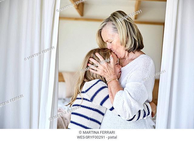 Grandmother kissing her granddaughter