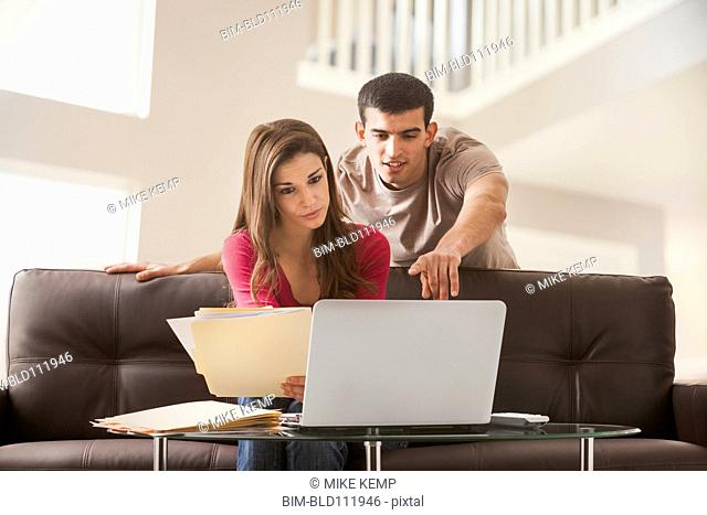 Couple reading papers at laptop together
