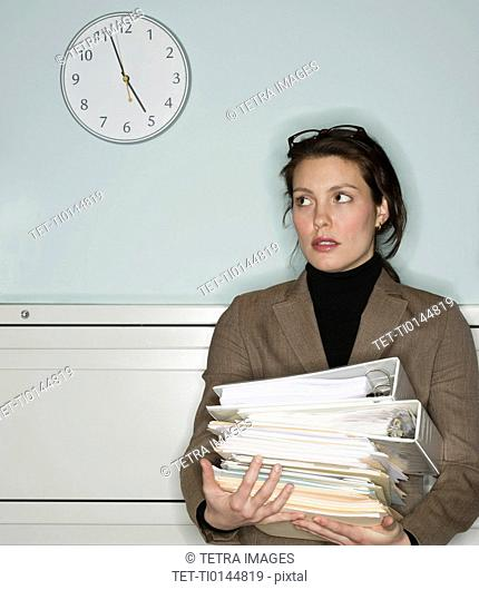 Young woman in office holding stack of documents