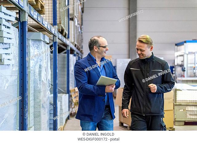 Manager and warehouseman dicussing logistics in storage