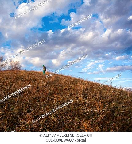 Boy on rural hillside looking down