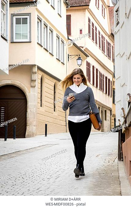 Germany, Tuebingen, smiling young student looking at cell phone while walking