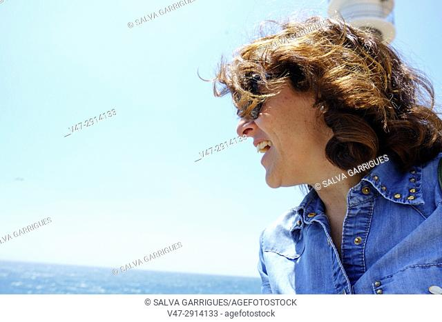 Portrait to a smiling woman contemplating the sea, Aguilas, Murcia, Spain