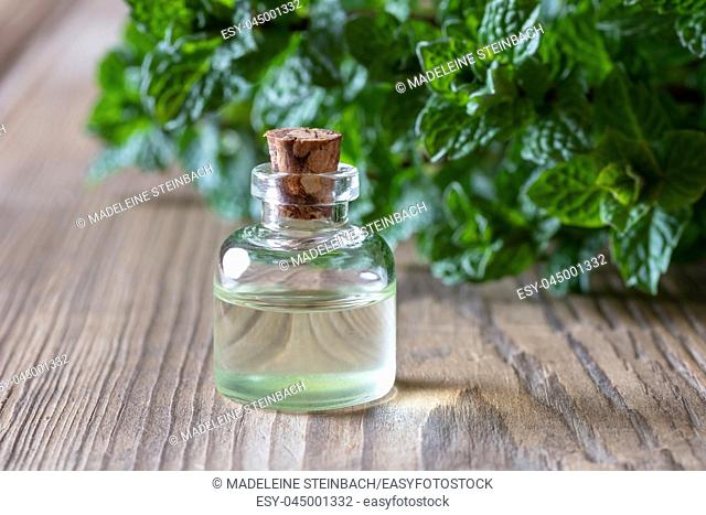 A bottle of essential oil with fresh peppermint leaves in the background