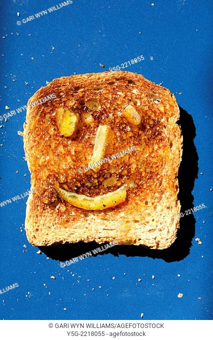 toasted bread with happy marmalade jam face on blue plate in sun