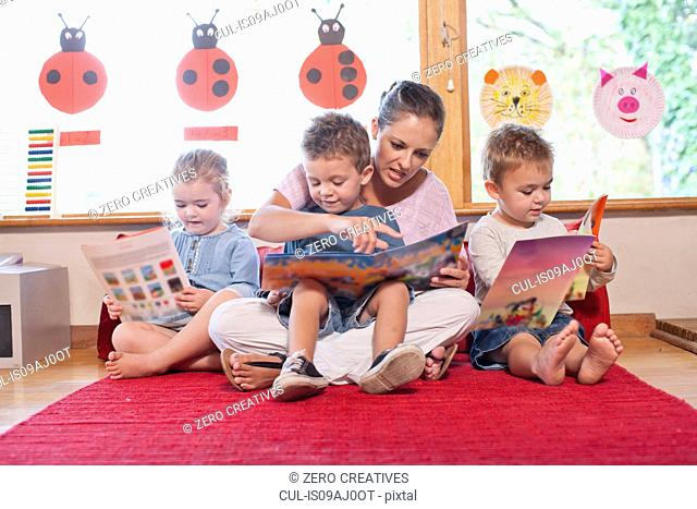 Teacher and pupils reading story books at nursery school