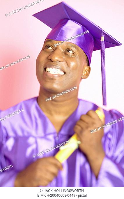 Man in cap and gown holding diploma