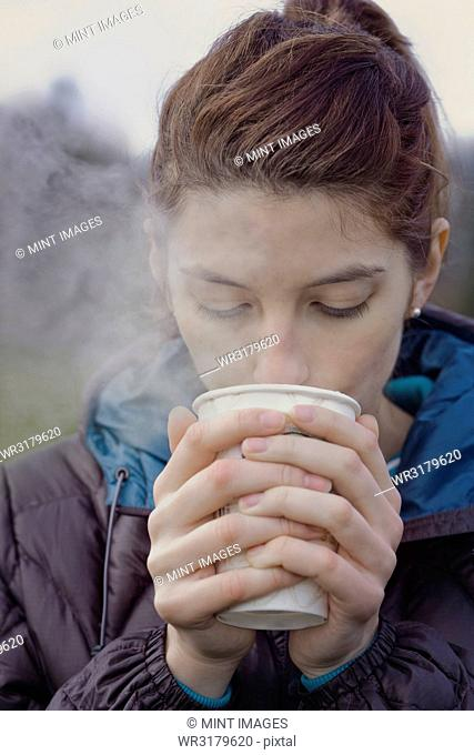 Caucasian woman drinking a hot cup of coffee on a winter day