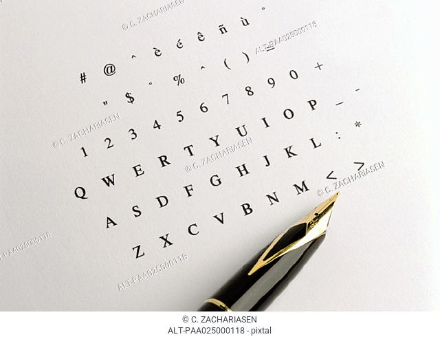 Numbers and alphabet printed on paper, tip of fountain pen
