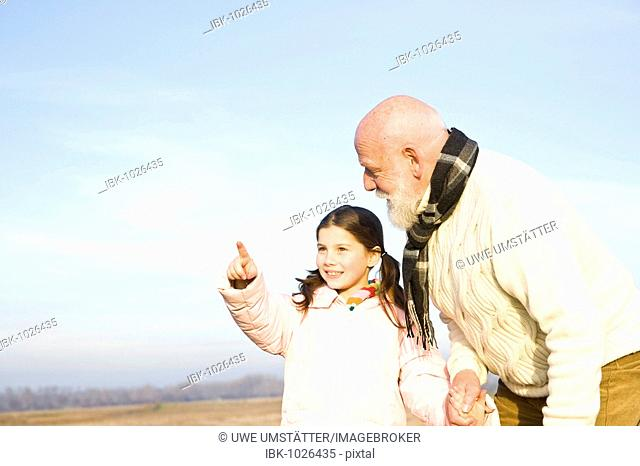 Girl showing her grandfather something in the distance