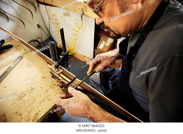 A bowman, a skilled man making a bow, in his workshop