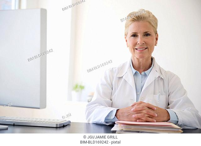 Caucasian doctor sitting at office desk