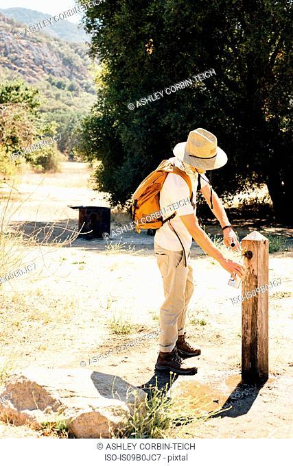 Man filling water bottle at outdoor tap, Malibu Canyon, California, USA