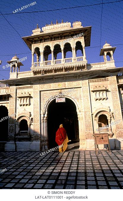 The Deshnok temple seen from the courtyard. A woman in a yellow sari and red veil crosses the marble paving going under the entrance arch