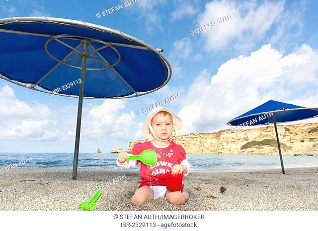 Toddler, girl wearing a sun hat playing in the sand with a shovel and a pail, beach of Triopetra, Crete, Greece, Europe