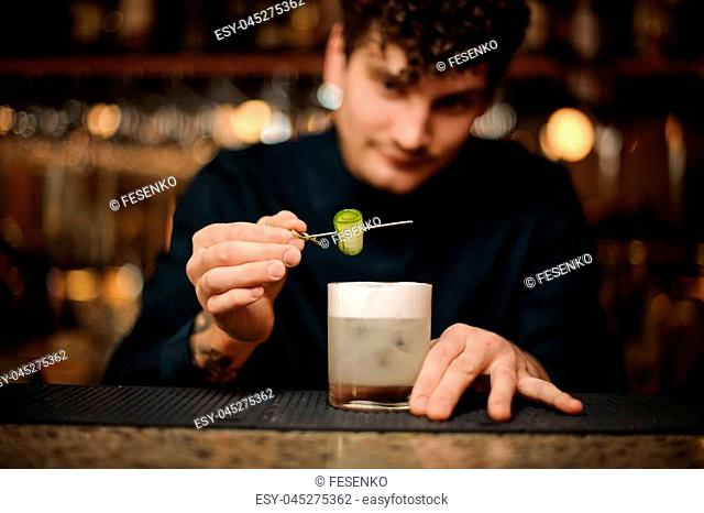 Bartender decorating a fresh cocktail with a fresh cucumber on a wooden skewer on the bar counter