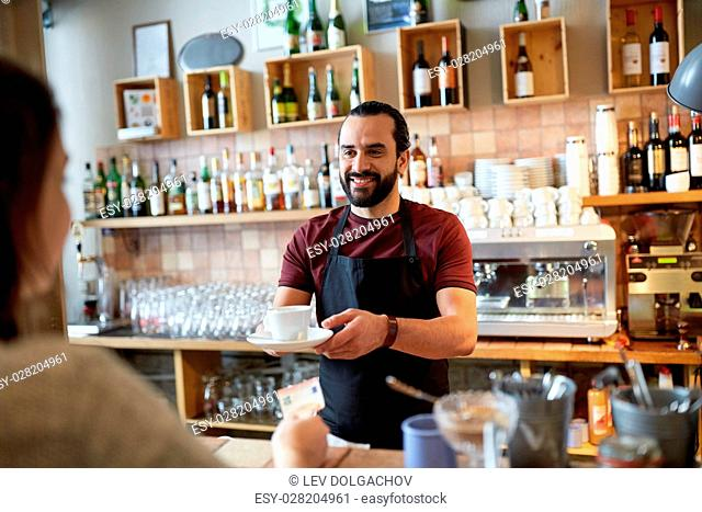 small business, people and service concept - happy man or waiter with coffee cup serving customer giving him money at bar