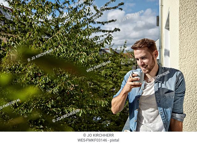 Smiling man drinking coffee on balcony