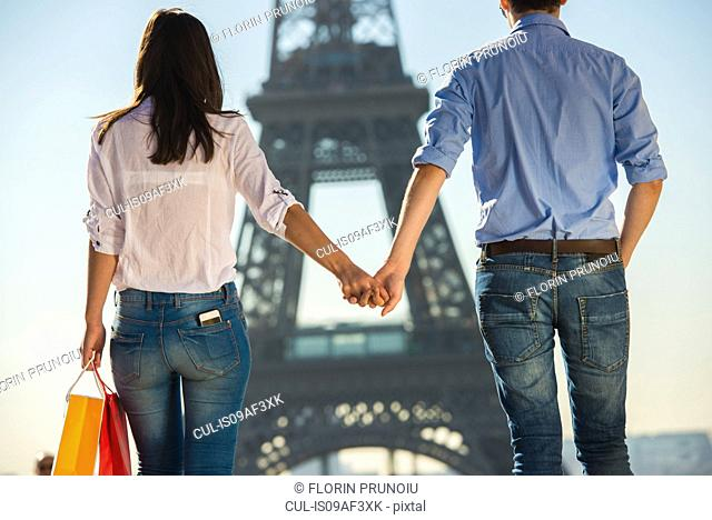 Young couple strolling in front of Eiffel Tower, Paris, France