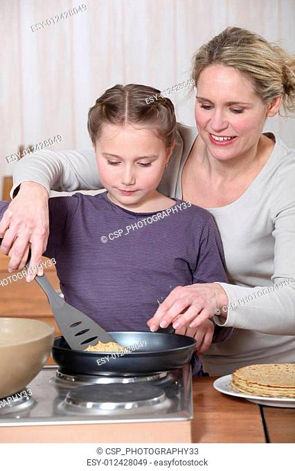Woman and little girl cooking pancakes