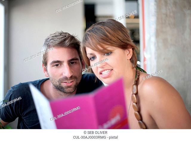 Young couple choosing from menu