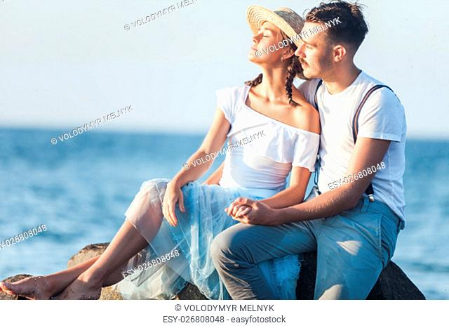Happy young romantic couple relaxing on the beach watching the sunset