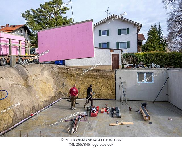 Prefabricated house, workers in setting up the basement walls on building site