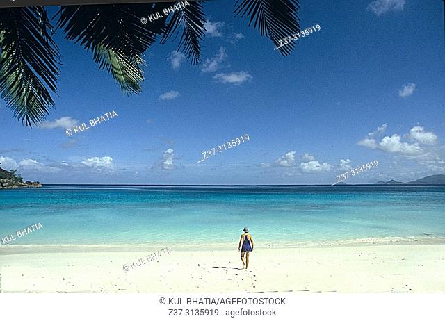 A mature woman walks toward the water on a white-sand beach of the Indian Ocean, Mahe, the Seychelles