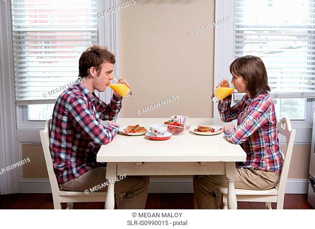 Young couple drinking orange juice at kitchen table