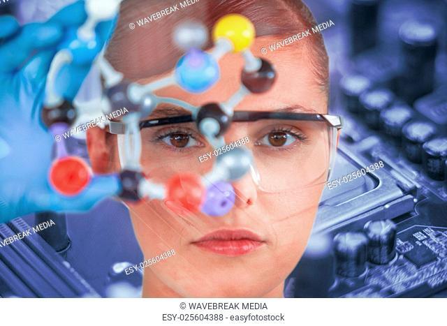 Composite image of portrait of female scientist holding molecular model