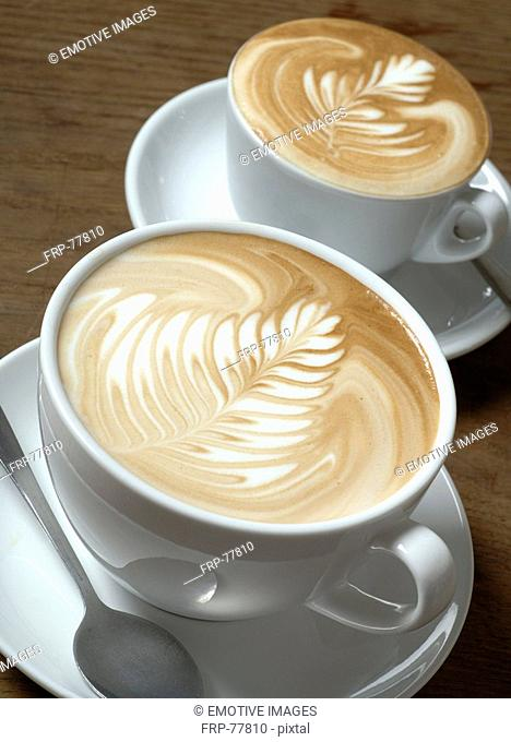 Two cappuccini with milk froth ornaments