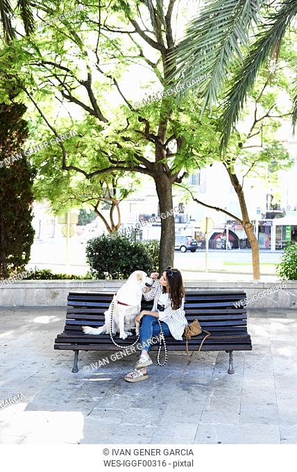 Young woman sitting on bench with her dog in the city