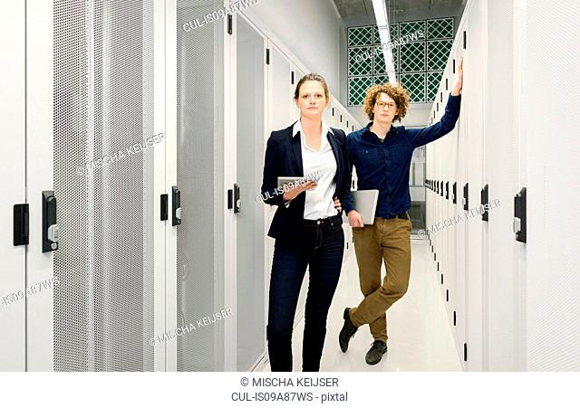 Two employees standing in data storage room