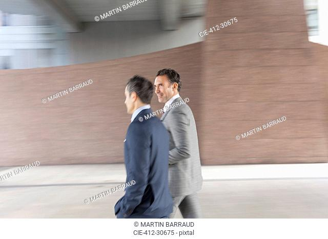 Corporate businessmen walking outside building
