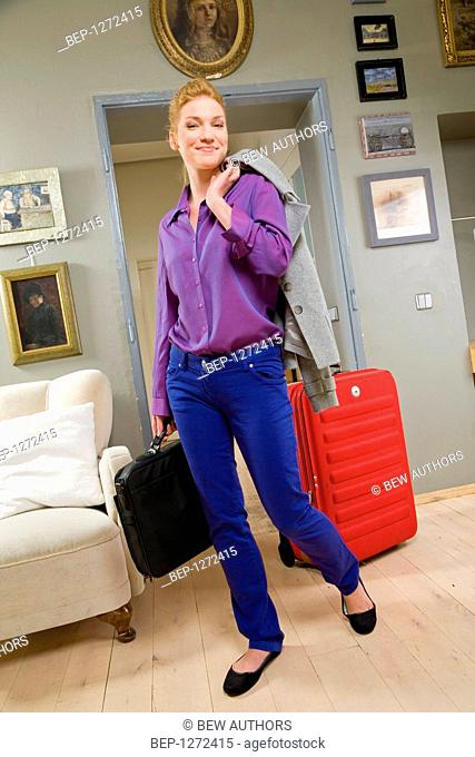 Woman going out with suitcase and laptop