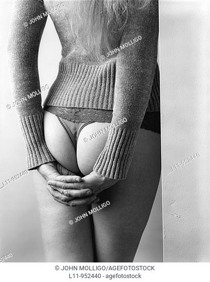 Woman in panties, from behind; leaning in corner