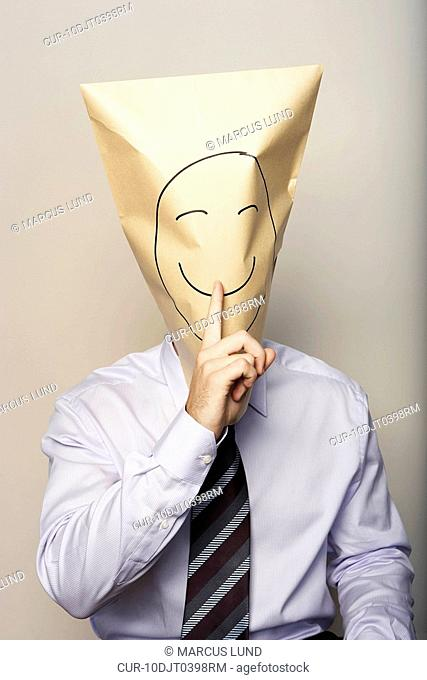 Business man with paper bag on head with a drawn smiling face gesturing quiet with his finger
