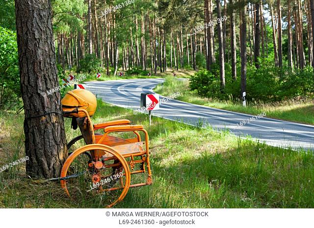 Creative warning of high-speed accidents by orange wheelchair, country road in Mecklenburg-Western Pomerania, Germany