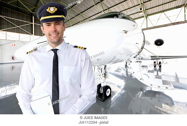 Smiling pilot standing in front of private jet in hangar
